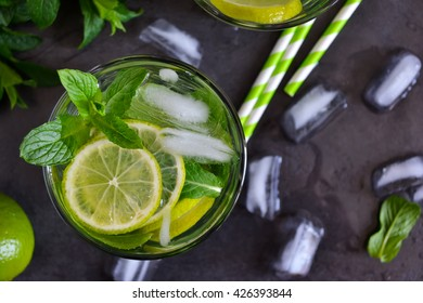 Mojito cocktail on black background with mint and lime