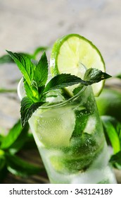 Mojito cocktail on wooden table closeup