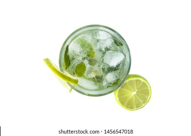 Mojito cocktail in a transparent glass with ice. Recipe for exotic drinks with mint, lime and white rum. Glass with a cocktail on a white background in the rays of the sun.