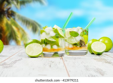 Mojito lime drinks on wood with blur beach background