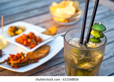 Mojito served in a glass with crushed ice and lime on wooden table