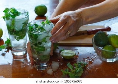 Mojito at a summer party. Homemade cocktail. Mint, rum, lime, soda.