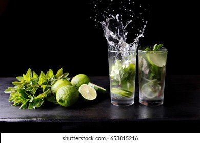 Mojito traditional beach refreshing cocktail alcohol drink in glass with splash, bar preparation soda water, lime, mint leaves, sugar, and rum. Dark black background with copy space for text