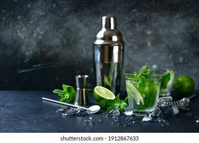 Mojito - boisson froide traditionnelle mexicaine à la chaux et à la menthe dans des lunettes sur fond d'ardoise sombre, de pierre ou de béton.