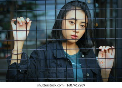 Mojokerto, Indonesia, Friday, 10 January 2020: A woman is behind an iron trellis