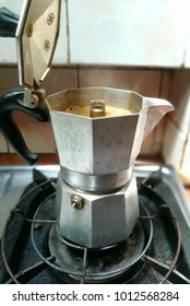 The moka coffee pot on the stove for Italian coffee, Italian traditional coffee maker with hot coffee flowing out from the spout, vintage color