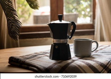 The moka pot is a stove-top or electric coffee maker that produces coffee by passing boiling water pressurized by steam through ground coffee.