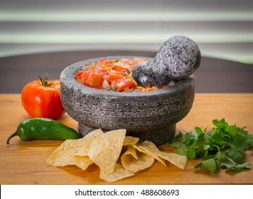 Molcajete with fresh salsa peppers Jalapenos tomato and cilantro also called a stone mortar, with chips.