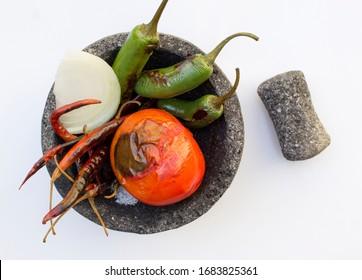 Molcajete with salsa of serrano peppers, tomato and onion, mexican stone mortar, cinco de mayo food celebration