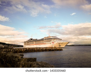 Molde, Norway - June 6, 2019: The cruise ship MSC Preziosa is located on Norwegian fjord in the port of Molde. Late evening in spring. Fjord and harbor wharf, moored ferry.