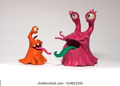 Molded from plasticine couple of funny monsters slugs. His tongue. Isolated on white background characters