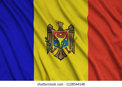 Moldova flag  is depicted on a sports cloth fabric with many folds. Sport team banner