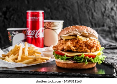 MOLDOVA, KISHINEV - November 27, 2018: Chicken burger with cheese, tomatoes, lettuce, sauce and can of coca cola, french fries on slate black background, lunch, close up