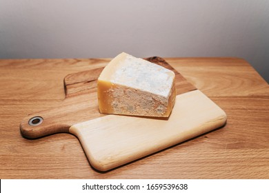 Moldy cheese on a cutting board, parmesan cheese with fungus, bad rotten food with dangerous microbes
