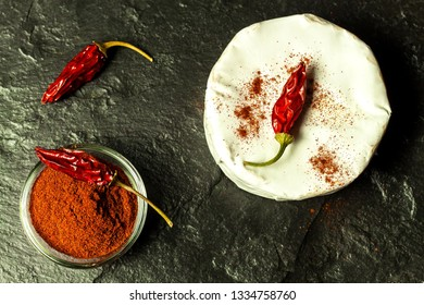 Moldy cheese and peppers on a black background. Dried chili peppers. Spicy moldy cheese.