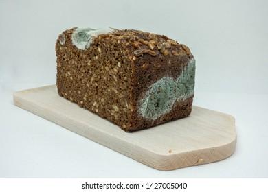 moldy rye bread lies on a wooden board