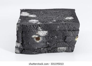 Moldy sliced black bread loaf over a white background.