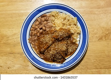 Mole with beans and rice, delicious typical Mexican food. Mole sauce with sesame seeds.