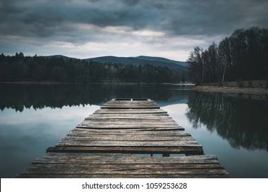 Mole (pier) on the lake.  Wooden bridge in forest in spring time with blue lake. Lake for fishing with pier. Dark and  Foggy lake with hills.