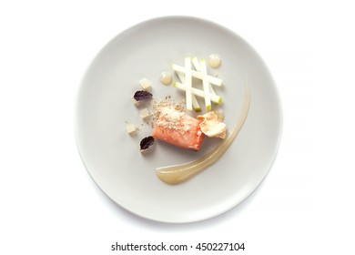 Molecular modern cuisine red fish in a dish with beautiful garnish close up. Isolated