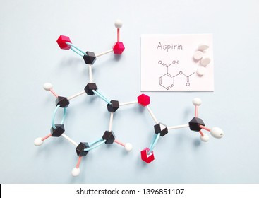 Molecular structure model of acetylsalicylic acid (aspirin, ASA) with tablets on bright background - C9H8O4. Structural chemical formula of aspirin written on the paper. Black=C, white=H, red=O.