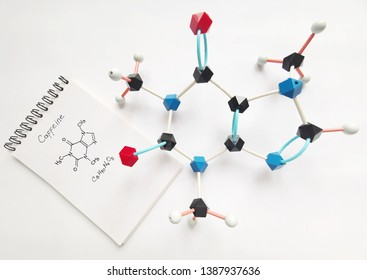 Molecular structure model of Caffeine molecule with written structural chemical formula in the notebook next to. Caffeine is a central nervous system stimulant, psychoactive drug.