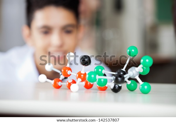 Molecular structure on desk with teenage boy looking at it in lab