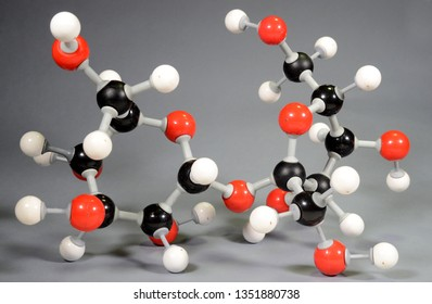 Molecule model of sugar (C12H22O11). Red is oxygen, black is carbon, and white is hydrogen.