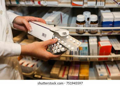 MOLNDAL, SWEDEN – AUGUST 02, 2012: Close up of hands holding a box of prescription drugs in a pharmacy. Selective focus.