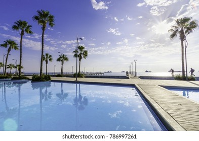 Molos Promenade and skyline of the coast in Limassol city in Cyprus at sunrise. View of the boardwalk pier path landmark with palm trees, pools of water, the Mediterranean sea and people walking.