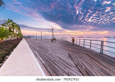 Molos Promenade and skyline of the coast in Limassol city in Cyprus at cloudy sunrise. View of boardwalk pier path landmark with palm trees, pools of water, the Mediterranean sea and people walking.