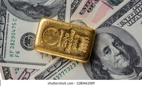 Molten gold bar weighing 250 gram against the background of dollar bills.