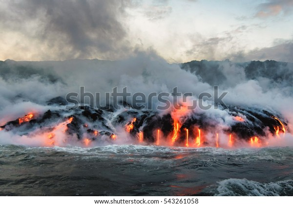 Molten lava flowing into the Pacific Ocean on Big Island of Hawaii, as ocean waves splash onto the rocks and flowing lava