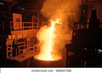 Molten steel being transferred from furnace to ladle in steel plant for further processing