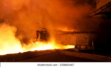 Molten steel pouring process with steam clubs at metallurgical plant. Stock footage. Close up fot steel pouring machine.