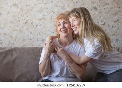 Mom and adult blonde daughter in white t-shirts hug on couch and laugh. Mother's day concept