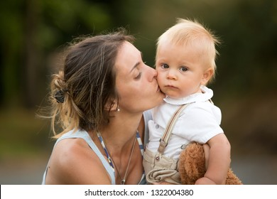 Mom and baby boy outdoor. Mother hug little son with love. Woman with child. Mothers day concept. Happy family enjoy sunny day. Love care and trust.