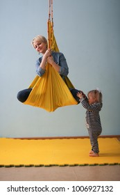mom and baby fun air yoga together, daughter shakes mom, yellow hammock. Lifestyle and Toning
