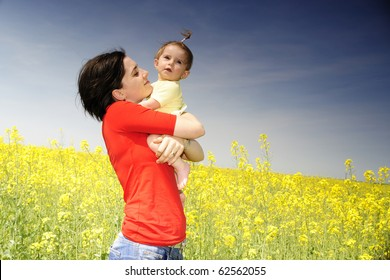 Mom and baby girl in a rapeseed field