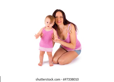 Mom and baby girl in the same pink clothes play on a white background