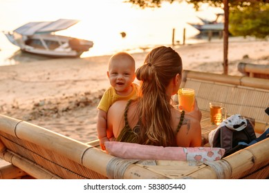 Mom and a baby have a rest in a cafe, Gili Meno, Indonesia