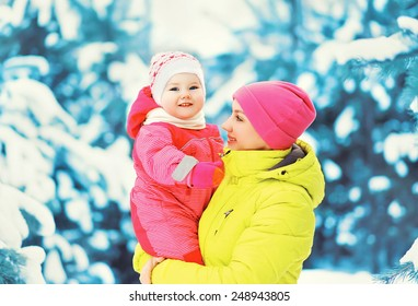 Mom and baby having fun outdoors in snowy winter day