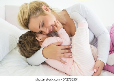 Mom and baby little girl in a gently hug in the bed.Shallow doff