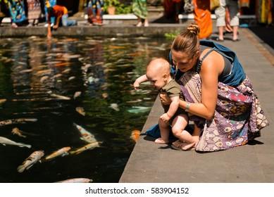 Mom and a baby near a pool with mirror carps, Pura Tirta Empul, Bali, Indonesia