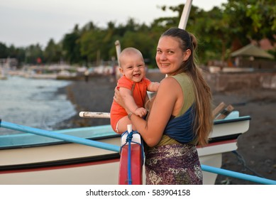 Mom and a baby on the black beach, Lowina, Bali, Indonesia