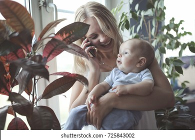 Mom with a baby on his hands talking on the phone, life style in a real interior, toning