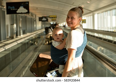 Mom and a baby on the moving walkway in airport