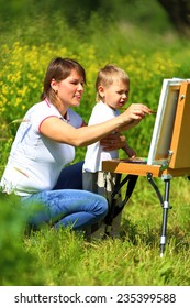Mom and baby paint on an easel in the field