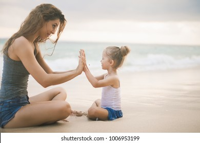 Mom and baby playing near the beach. Traveling with your family, child. Games with child affect early development. Important to spend enough time with your kids.