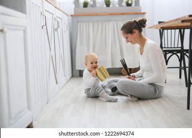 Mom and baby playing together on the kitchen floor, living style in a real Scandinavian-style interior.
